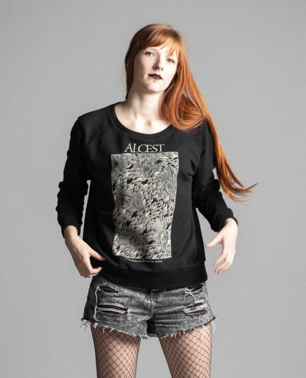 C'est un pull noir femme de la marque Radio Metal en lien avec la sortie du livre : Alcest, L'intégrale by Radio Metal pour le groupe de musique metal Alcest dont le visuel est fait par Fortifem et représente un paon.