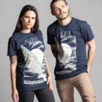 C'est un t-shirt bleu femme et homme de la marque Radio Metal en lien avec la sortie du livre : Alcest, L'intégrale by Radio Metal pour le groupe de musique metal Alcest dont le visuel est fait par Fortifem et représente une main et une aile avec une lune.