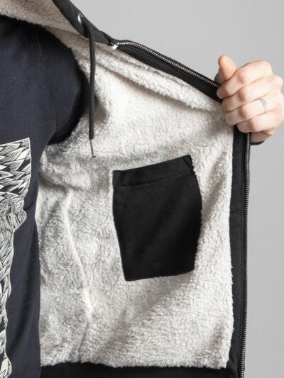 C'est la poche intérieure de la veste sherpa à capuche noire femme et homme de la marque Radio Metal qui représente un chat satanique
